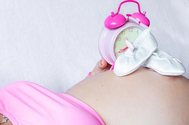 Kaukasische zwangere vrouw die met babyballetschoenen en roze en witte wekker over haar buik ligt