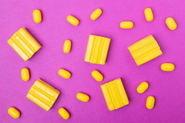 Kauwgom, gele dragee op felroze.