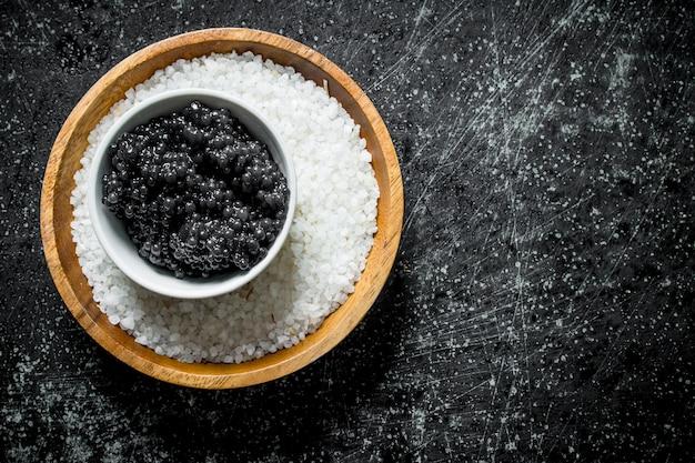 Kaviaar en zout in de kommen. op zwarte rustieke tafel