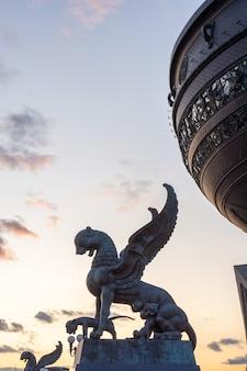 Kazan, tatarstan, rusland - 28 september 2019. het beeldhouwwerk van een gevleugelde sneeuwluipaard (ak bars, aq bars) met welpen, het symbool van tatarstan in de buurt van het kazan-huwelijkspaleis. zonsondergang.