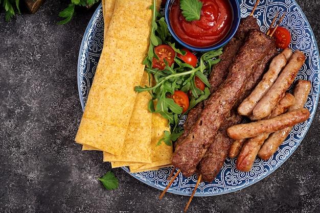 Kebab adana, lamsvlees en rundvlees op lavashbrood met tomatensaus