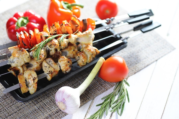Kebab gekookt op metalen spiesjes met groenten geserveerd op witte tafel
