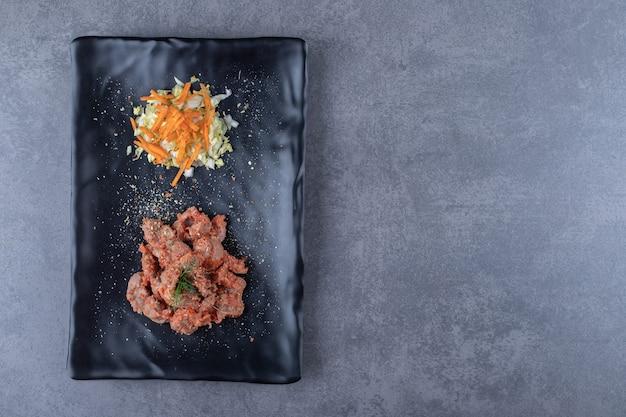 Kebab stukken en salade op zwarte plaat.