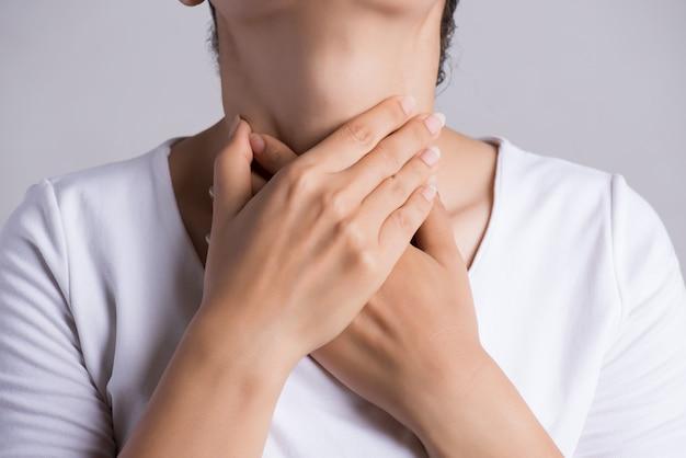 Keelpijn. jonge vrouwenhand wat betreft haar zieke hals. gezondheidszorg concept.