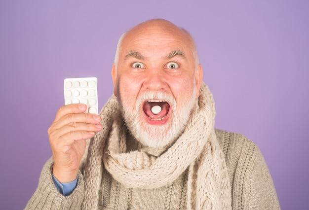Keelpijn man met pillen van keelpijn behandeling pil geneeskunde oude man die geneesmiddelen neemt