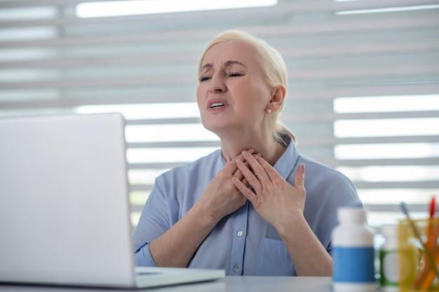 Keelpijn. ongelukkige blonde vrouw die een laptop scherm bekijkt dat haar keel houdt die toont waar het pijn doet.