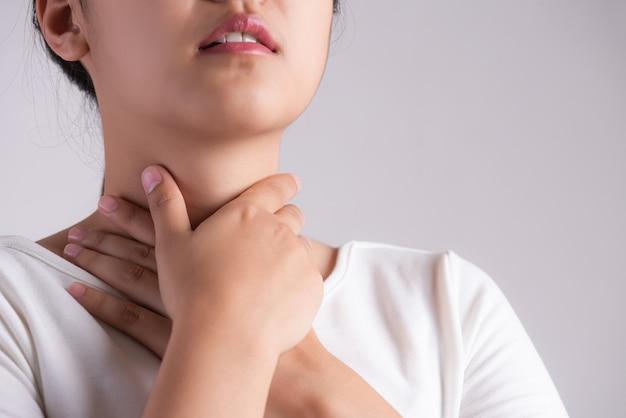 Keelpijn. vrouwenhand wat betreft haar zieke hals. gezondheidszorg concept.