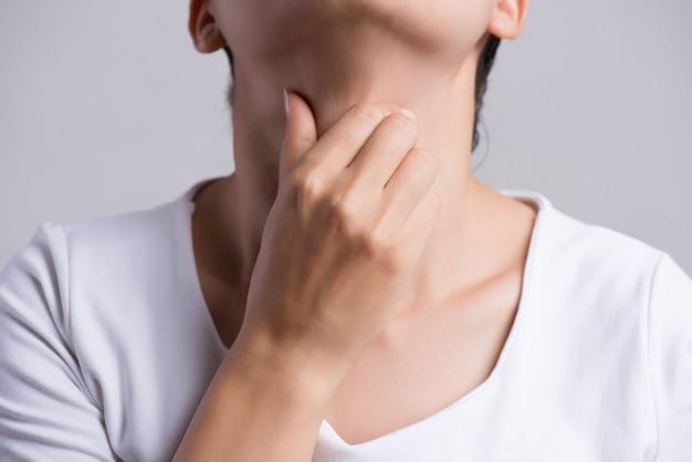Keelpijn. vrouwenhand wat betreft haar zieke hals. gezondheidszorg en medisch concept.