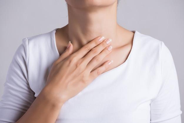 Keelpijn. vrouwenhand wat betreft haar zieke hals. gezondheidszorg en medisch.