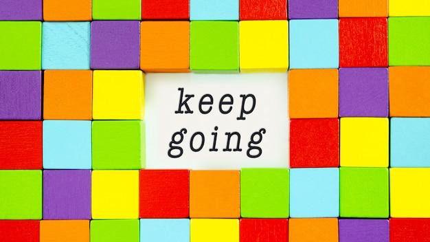 Keep going getypt op wit papier omringd door kleurrijke blokken in een conceptueel beeld van inspiratie en motivatie.