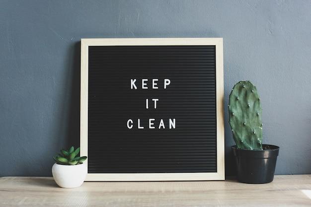 Keep it clean citaat op bord met cactus en sappig op houten tafel
