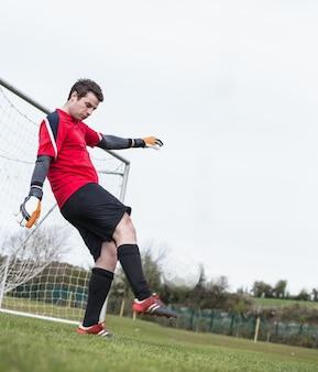 Keeper in rode bal schoppen uit de buurt van doel