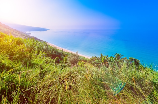 Kefalonia-eiland. rustige lange stranden aan de zuidkant van kefalonia. ochtendzonvlammen verschijnen over de heuvel