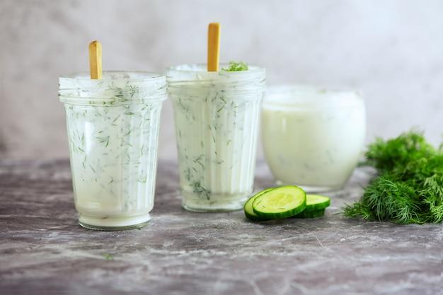 Kefirdrank met dille en komkommer op grijs