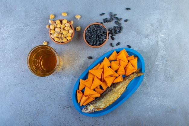 Kegelchips en gedroogde vis op een houten bord op een handdoek, op het marmeren oppervlak.