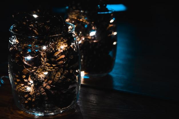 Kegels met guirlande in glazen vaas kerstmis kerstvakantie nieuwjaar winterlicht feestelijke decoraties