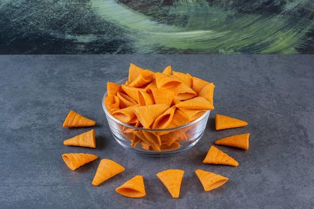Kegelvormige chips in een glazen kom op het marmeren oppervlak