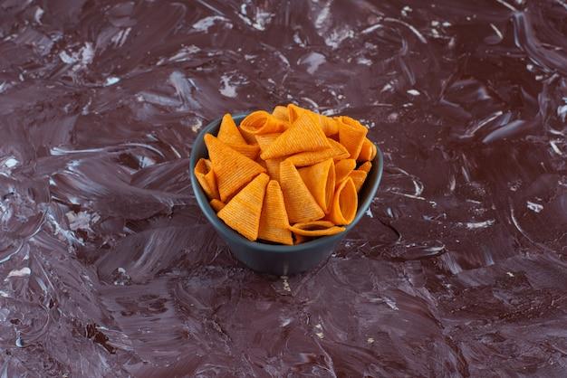 Kegelvormige chips in een kom op het marmeren oppervlak