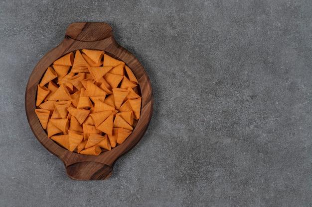 Kegelvormige maïschips met kaassmaak in houten plaat op het marmeren oppervlak