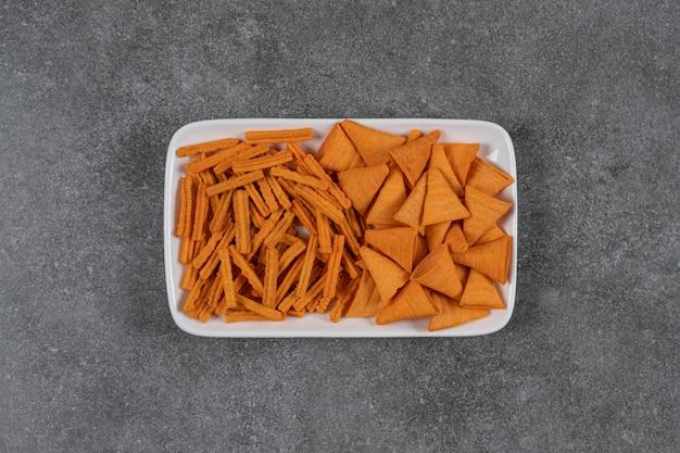 Kegelvormige maïsspaanders met gedroogde broodkaas op smaak gebracht in plaat op het marmeren oppervlak