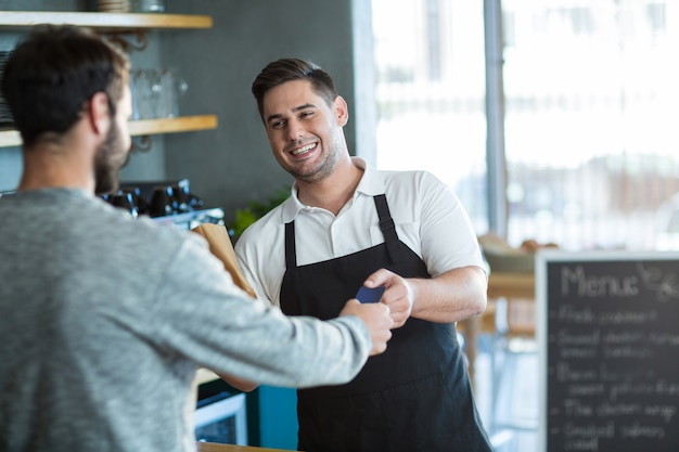 Kelner die brood geeft aan klant bij teller