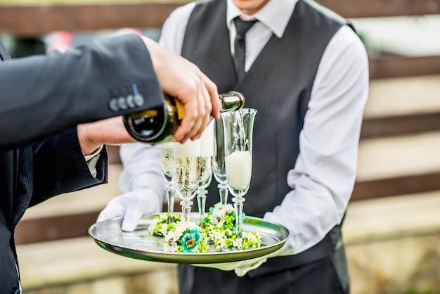 Kelner die dienblad met glazen houden
