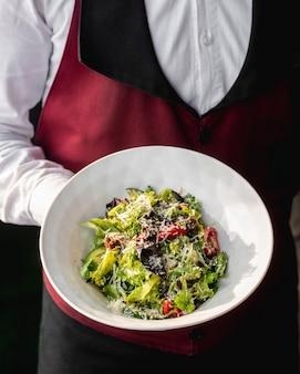 Kelner die een plaat van groene salade met gedroogde tomaat houdt