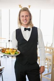 Kelner die een plaat van voedsel in restaurant houdt