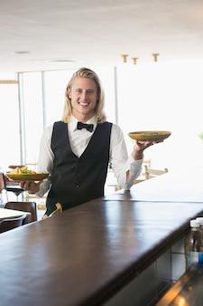 Kelner die geplateerde maaltijden in restaurant houdt