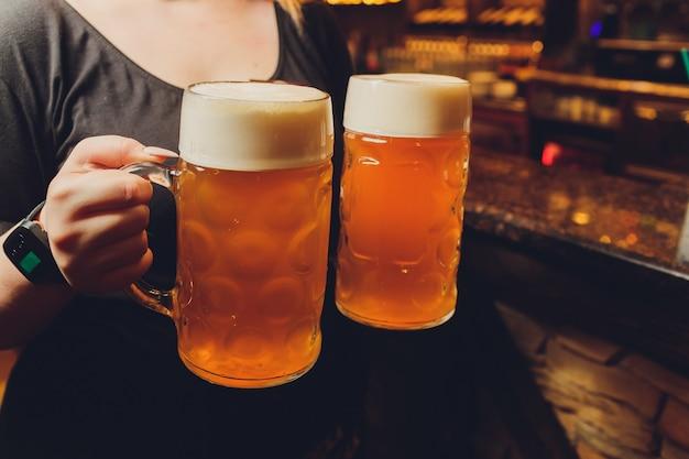 Kelner die glazen koud bier op het dienblad dienen.