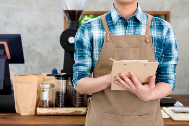 Kelner die orde neemt bij koffiewinkel