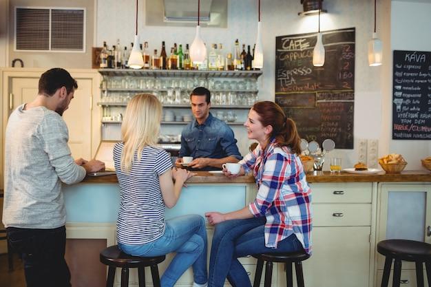 Kelner die vrouwelijke klanten bekijken die bij teller in koffie zitten
