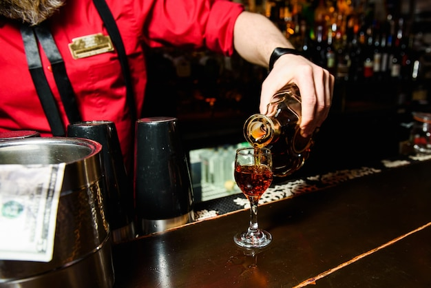 Kelner in rood giet whisky in een glas