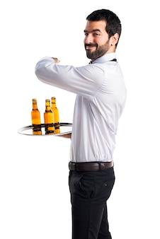 Kelner met bierflessen op de bak naar voren wijzen