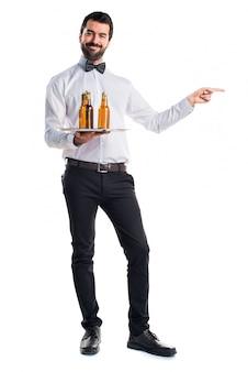Kelner met bierflessen op de lade die naar de zijde wijst