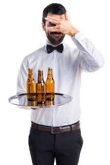 Kelner met bierflessen op de lade die zijn gezicht bedekt
