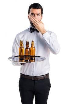 Kelner met bierflessen op de lade die zijn mond bedekt