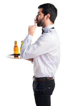 Kelner met bierflessen op de lade waardoor stilte gebaar is