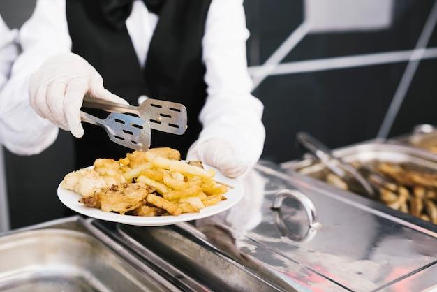 Kelners dienende plaat van voedsel met tang