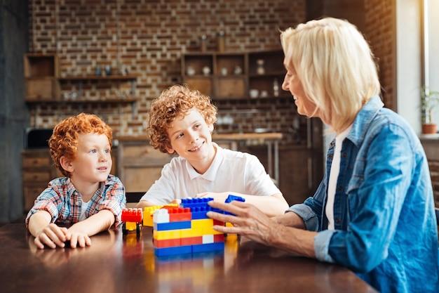 Ken jij. selectieve aandacht voor twee schattige broers die glimlachen terwijl ze aandachtig naar hun grootmoeder kijken en naar haar verhalen luisteren