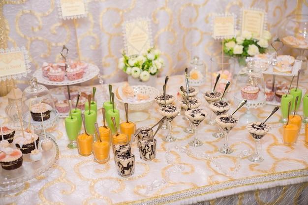Kendybar met room-soufflé in glazen op tafel voor snoep