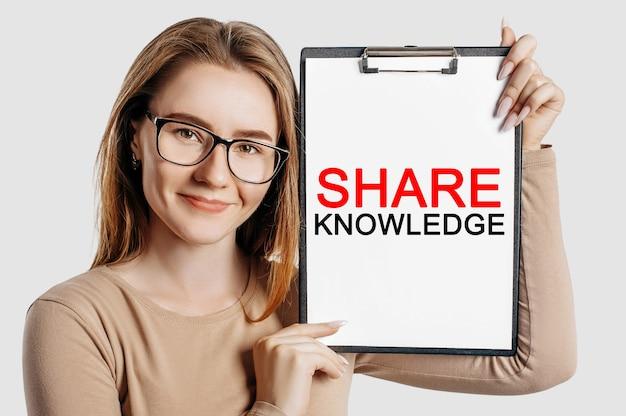 Kennis delen. mooie jonge zakenvrouw met een bril houdt een klembord vast met mock-up ruimte geïsoleerd op een grijze achtergrond