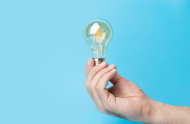 Kennis en idee concept gloeilamp met licht in de hand op een lege blauwe achtergrond hersenen wijsheid kno ...