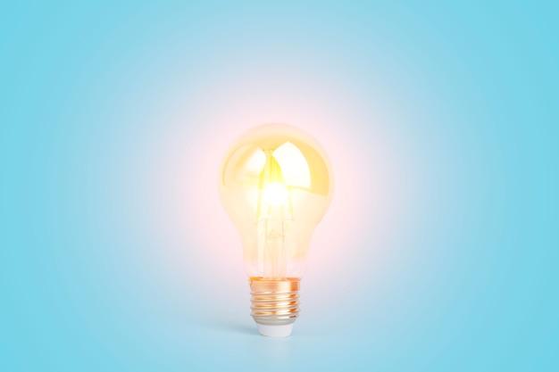 Kennis en idee concept gloeilamp met licht op een lege blauwe achtergrond hersenen wijsheid kennis een...
