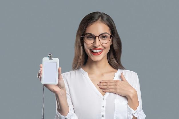 Kennis. glimlachende jonge bedrijfsvrouw die glazen met kenteken draagt die in uitstekende stemming kennis maken