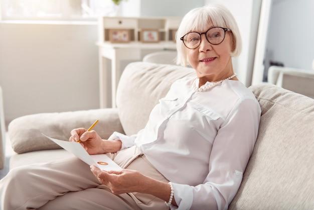 Kennis is macht. mooie vrolijke oudere vrouw zittend op de bank en de grafieken op de afdruk te onderzoeken, meer te leren over de huidige economische situatie