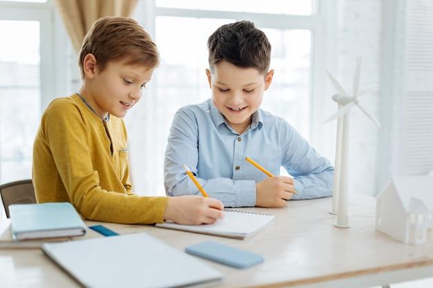 Kennis opdoen. vrolijke pre-tienerjongens die aan tafel zitten en samen windturbines schetsen in hun notitieboekje, terwijl ze leren over alternatieve energiebronnen