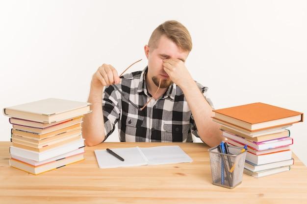 Kennis student en onderwijs concept vermoeide man zit aan de tafel en maakt aantekeningen in een notitieblok
