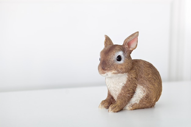Keramiek beeldje van bunnyisolated op witte muur. close-up van bruin beeldje van een paashaas. porseleinen konijntje. pasen-decoratie - ceramisch pasen-konijn op witte muur. kopieer ruimte. tekst