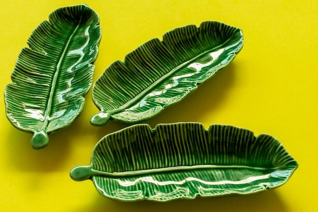 Keramiek in de vorm van groen blad op gele achtergrond